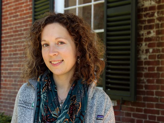 Candid headshot of VVCR Office Manager Amanda Hurley. A woman with dark curly hair poses in front of an historic brick home on the grounds of Virginia's Brownsville Preserve.