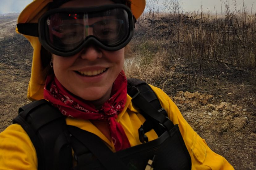 A woman wearing yellow fire retardant gear and thick goggles takes a selfie during a controlled burn. She is standing in front of an open scrubby piece of land that has not yet been ignited.