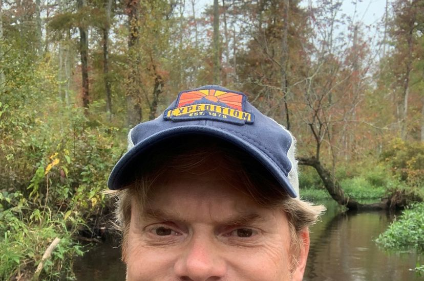 Candid headshot of VA Chesapeake Bay program director Andy Lacatell. A smiling man wearing a cap and flotation device poses on the water in a wooded wetland.
