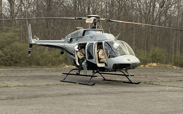 A silver helicopter sits on the tarmac prior to spinning up the rotors and taking off. Two people are sitting in the cockpit. A third person sits in the open door looking up.
