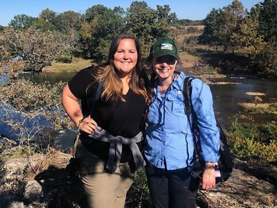 Two women stand at an overlook with a river and trees behind them.