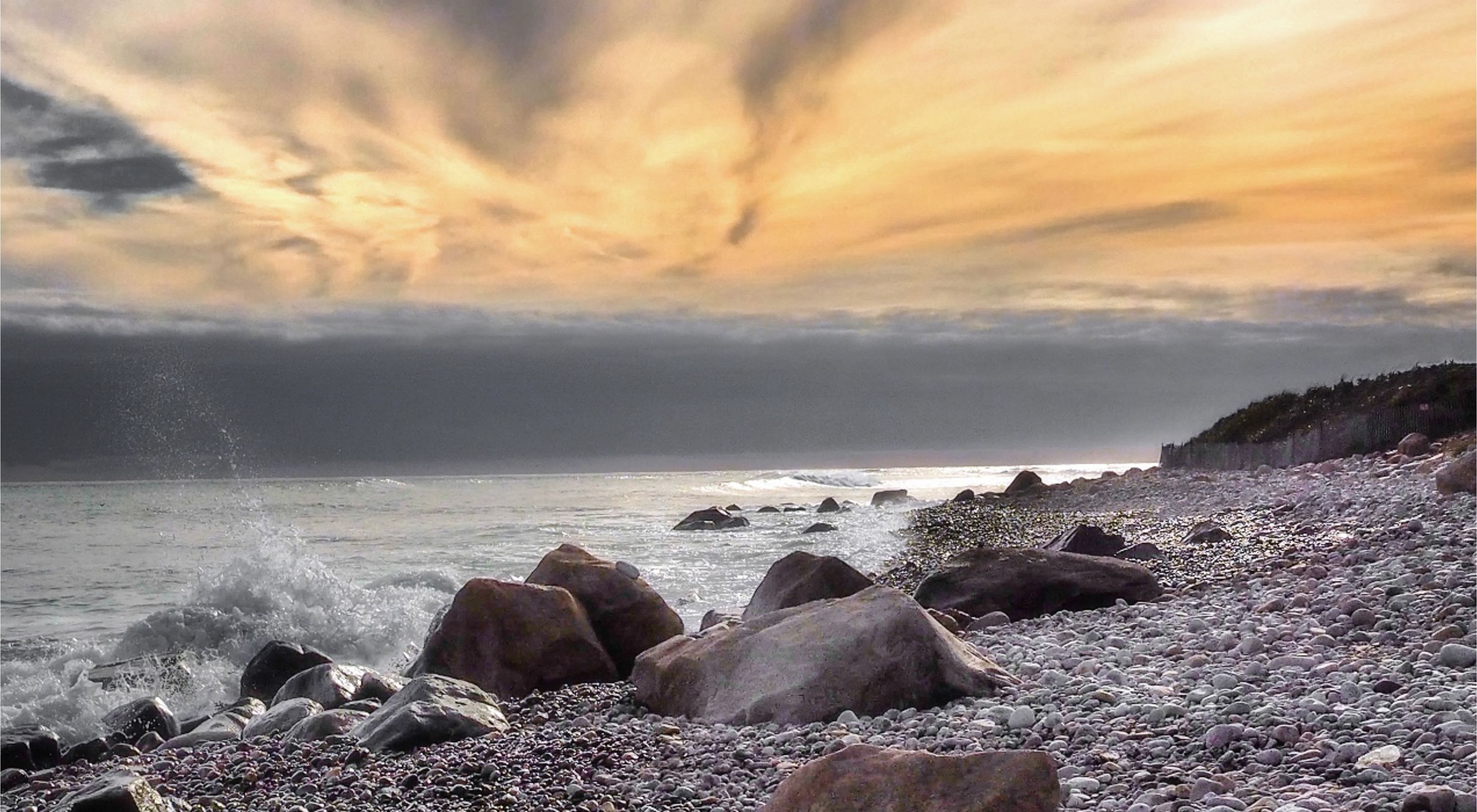 A beach filled with various rocks on the right hand side with small ocean waves breaking on the shoreline on the left hand side, with a yellow sunset skyline in the background.
