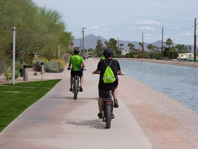 People bike along canal in AZ