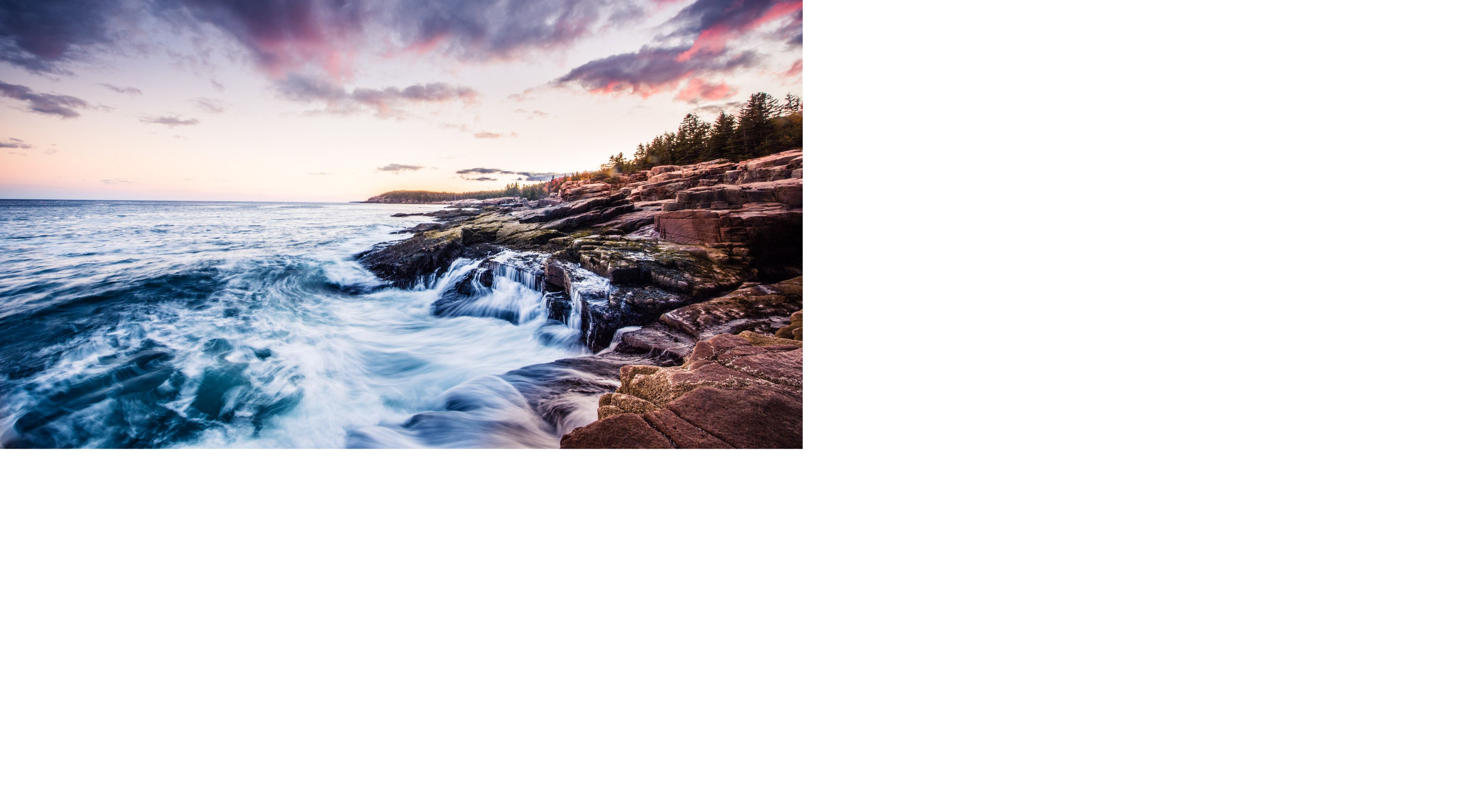 Waves crashing against the rocky coast of Acadia National Park at sunset, Maine. In 2016, the National Park Service celebrated their 100 year anniversary.