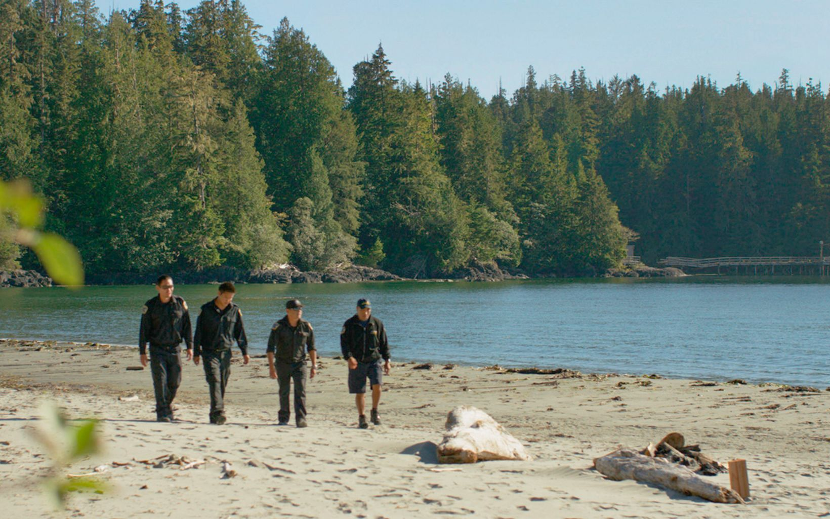 Across Canada, Indigenous guardian programs are essential for stewardship of land and water. Ahousaht Watchmen walk across beach in Canada.