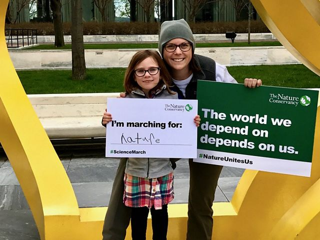 """A woman at right with a sign in her hand saying """"The world we depend on depends on us."""" next to a younger individual holding a sign saying """"I'm marching for nature."""""""