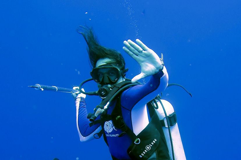 A man scuba dives in the Pacific, seeming to be suspended in air as he floats against a dark blue background. He strikes a dramatic pose with one hand stretched out in front of him.