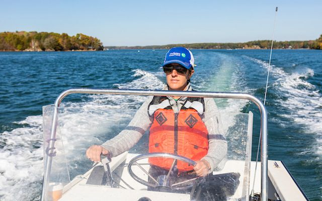 The Nature Conservancy's Alix Laferriere drives a boat to the oyster restoration reef in Great Bay that is part of the Supporting Oyster Aquaculture and Restoration (SOAR) program on Great Bay in Durham, New Hampshire.