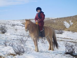 A woman sits atop her horse on snow-covered grasslands in Mongolia