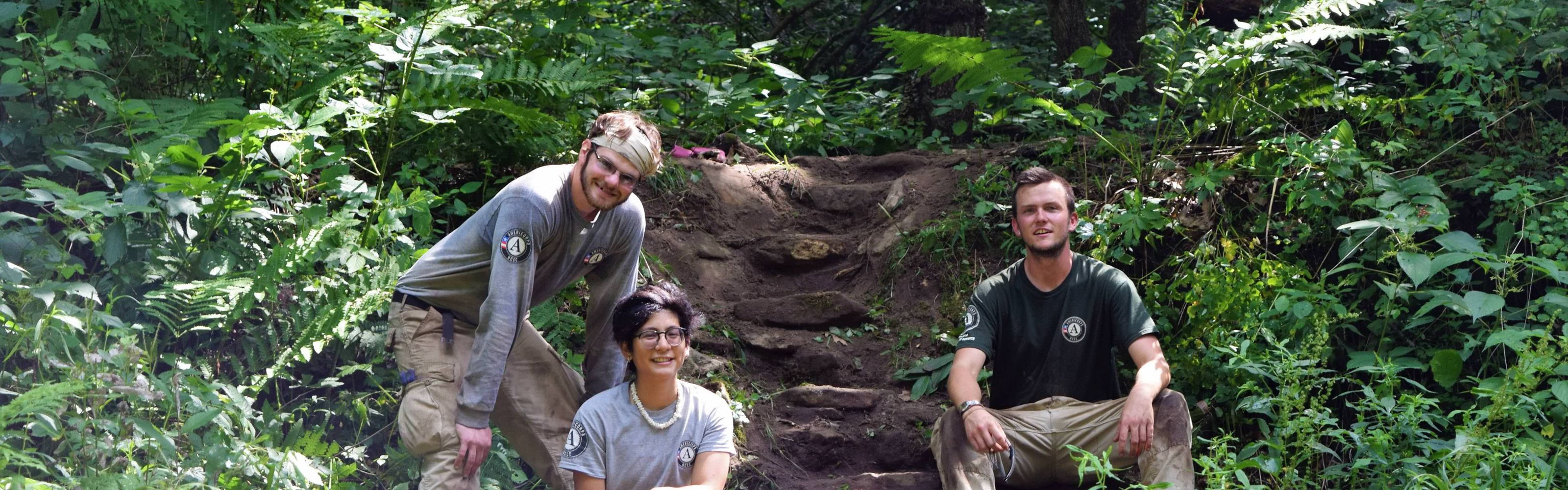 AmeriCorps volunteers pose with a new rock staircase.