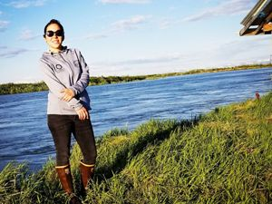A woman stands on a grassy bank in front of an Alaskan waterway