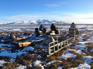 People sit on snowmobiles in a melting snow landscape