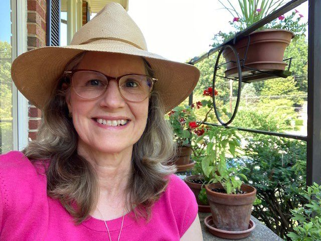 Candid snapshot of Associate Director of Philanthropy Anne MacGlashan. A smiling woman wearing a wide brimmed straw hat snap a selfie while sitting on an outdoor patio filled with plants.