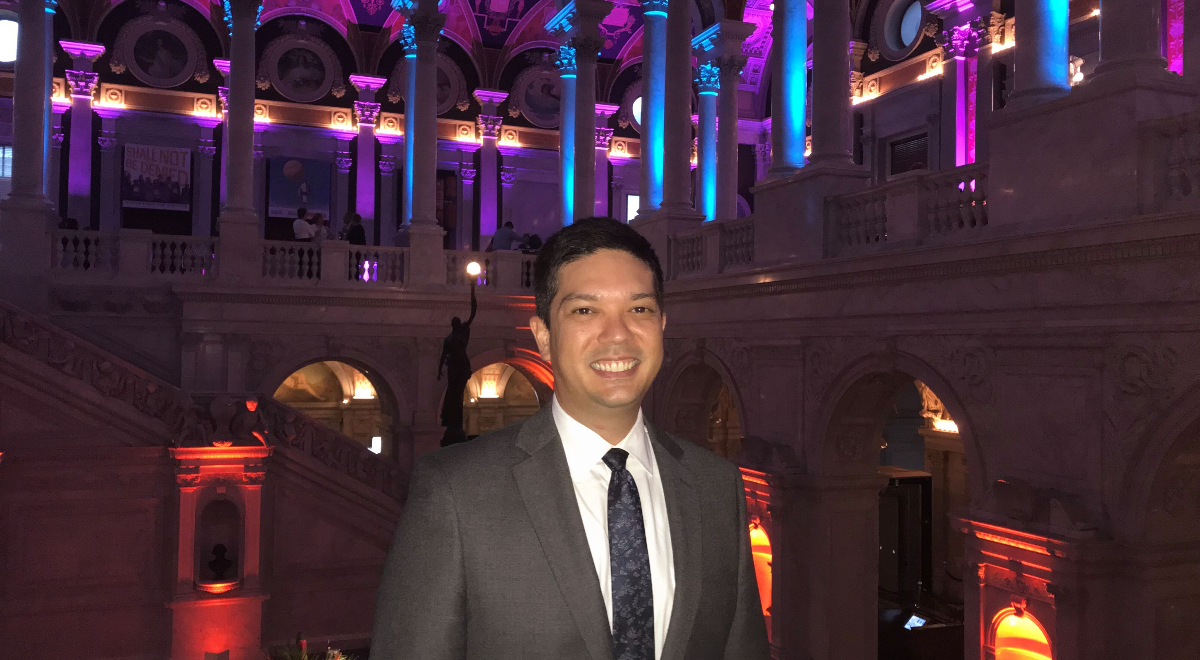 Anthony Ching wearing a black suit stands in a building list with blue and purple lights.