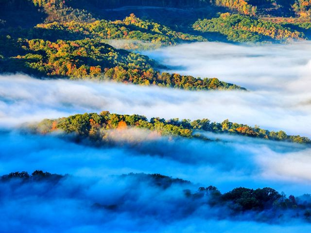 A mist rises up in between forested ridges.