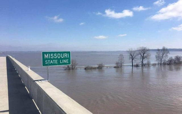 A Missouri State sign along the highway surrounded by flood water.