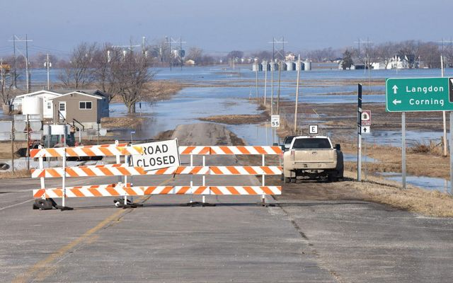 A road closed barricade blocks traffic from entering flooded areas.