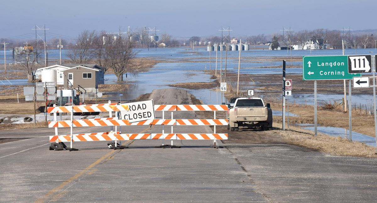 Flood waters over road with barricade closing the road.