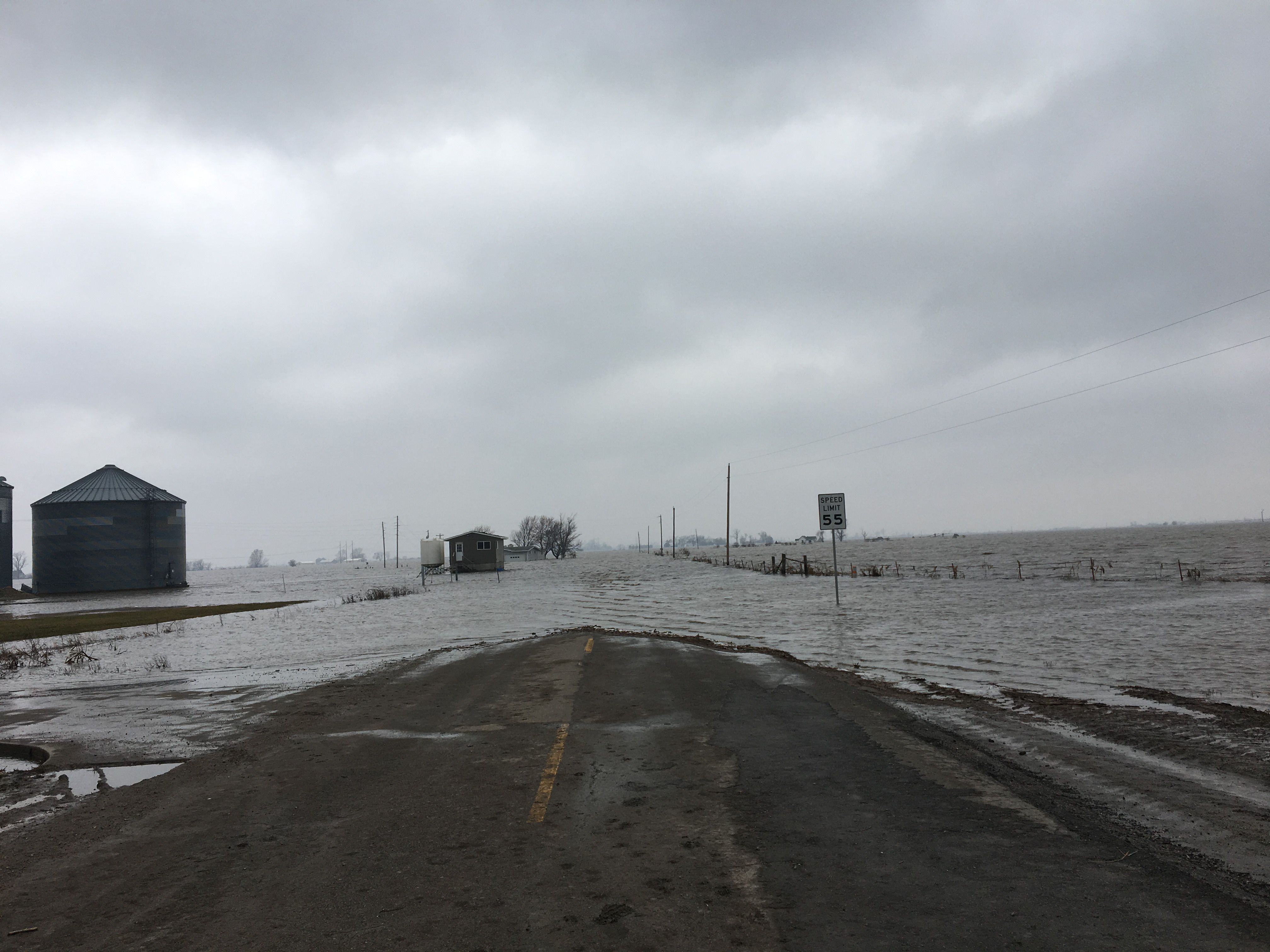 Water flooded over road and farm buildings.