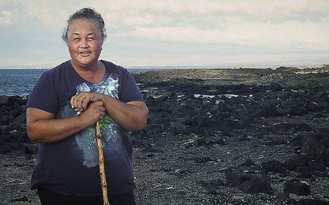 "Leina'ala ""Aunty Lei"" Lightner stands on a rocky shore in Hawaii."