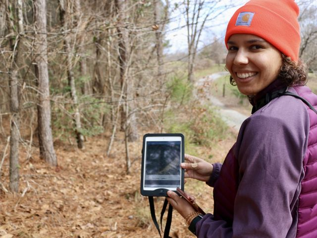 Lauren Goodman stands by a forest tract holding a tablet.