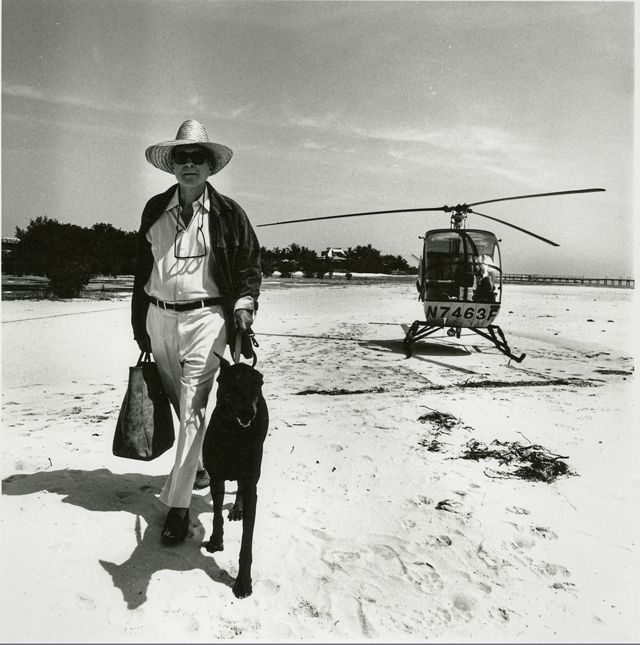 black and white image of stylish man with dog walking on sand away from a helicopter