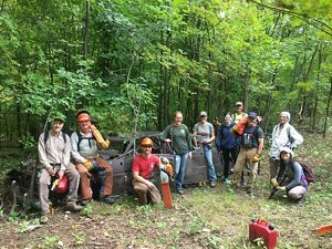 A group of TNC staff and volunteers standing with tools in a forest.