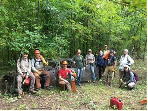 Volunteer crew posing with tools with forest background