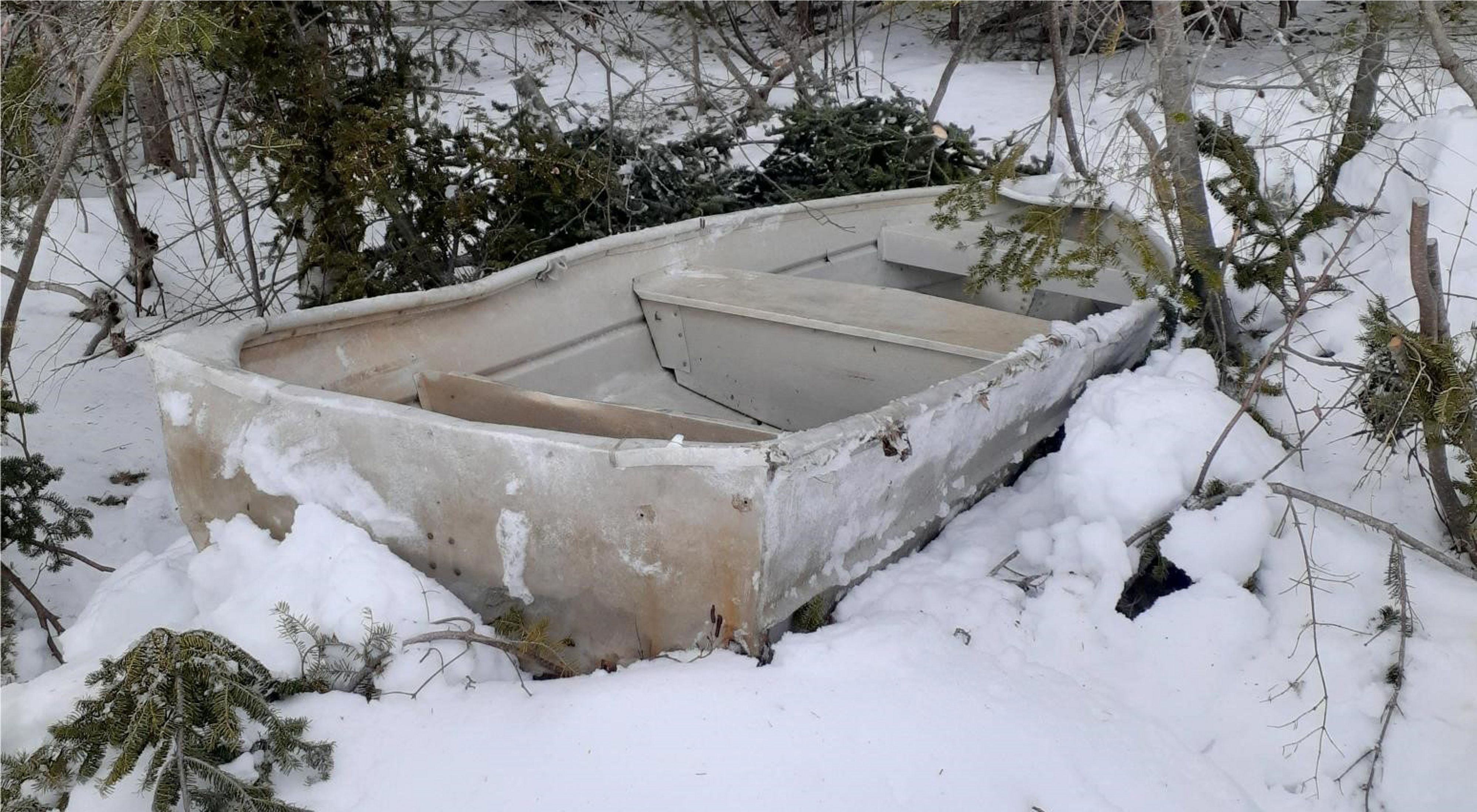A dented aluminum boat sits in snow in the woods.