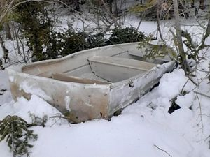 A dented aluminum skiff lies abandoned in the snow.