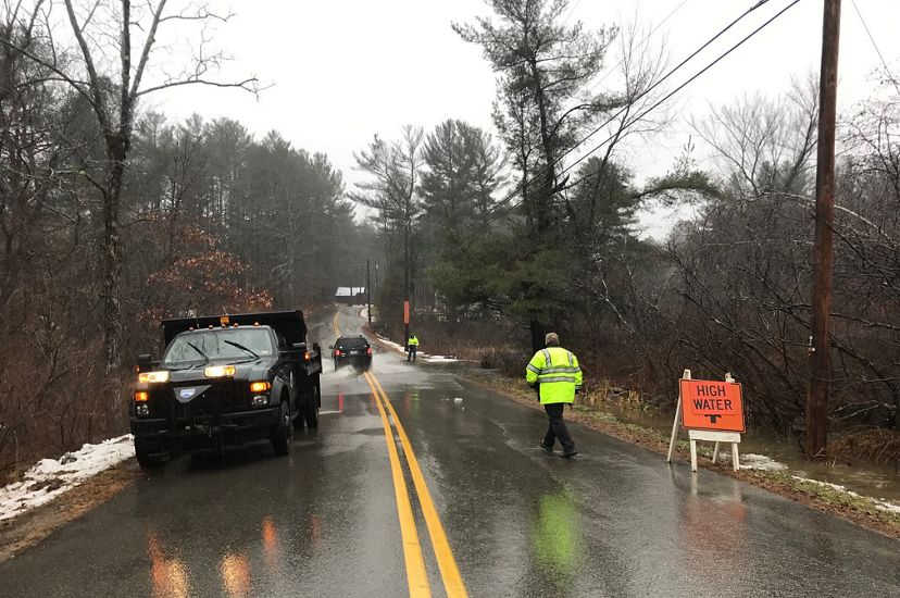 A wet road with a utility truck and a worker in a reflective vest.