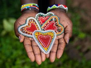 Hands hold beaded hearts made by artisans in Kenya