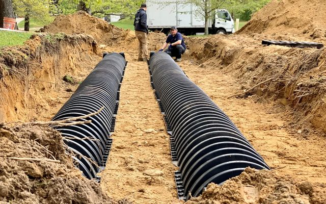 A shallow ditch with two, long parallel black plastic conduits in it.