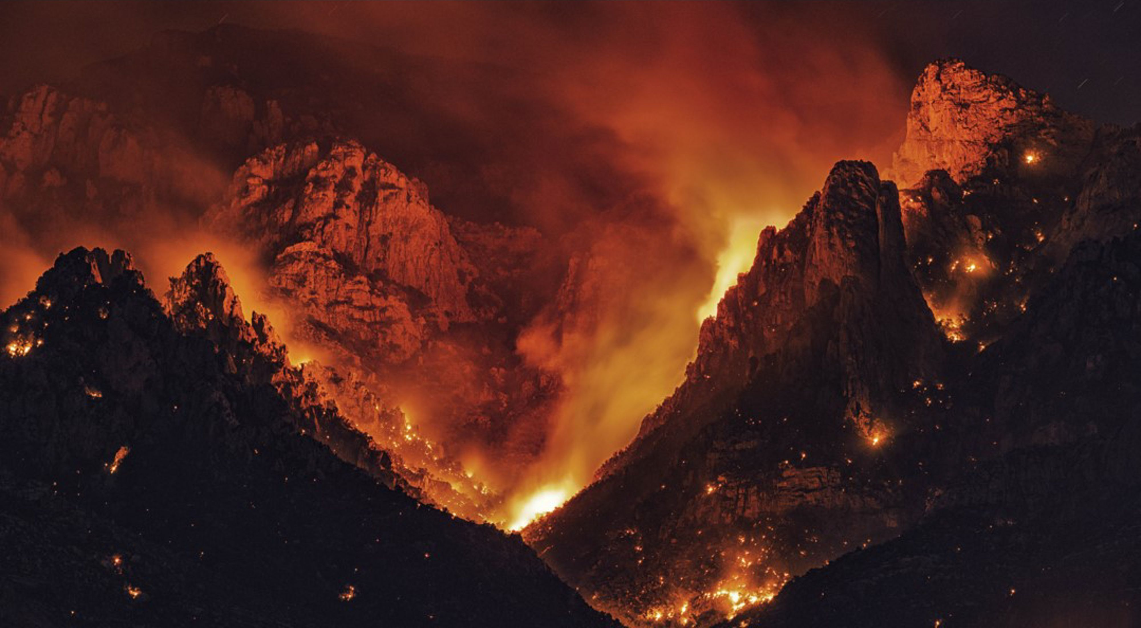 Bright orange fire glows out from between mountains at night.