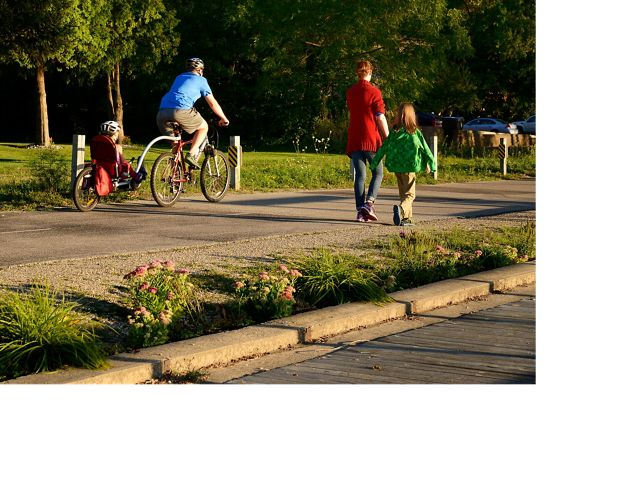 Man on a tandem bike with child in the back and woman with a second child walk along a trail bordered by planted pink flower