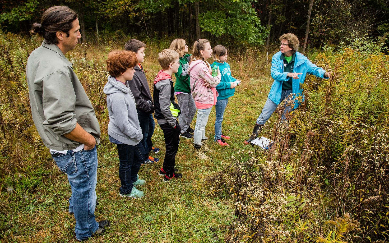 A woman in a blue jacket points toward tall plants and talks with a group of children in the fall.