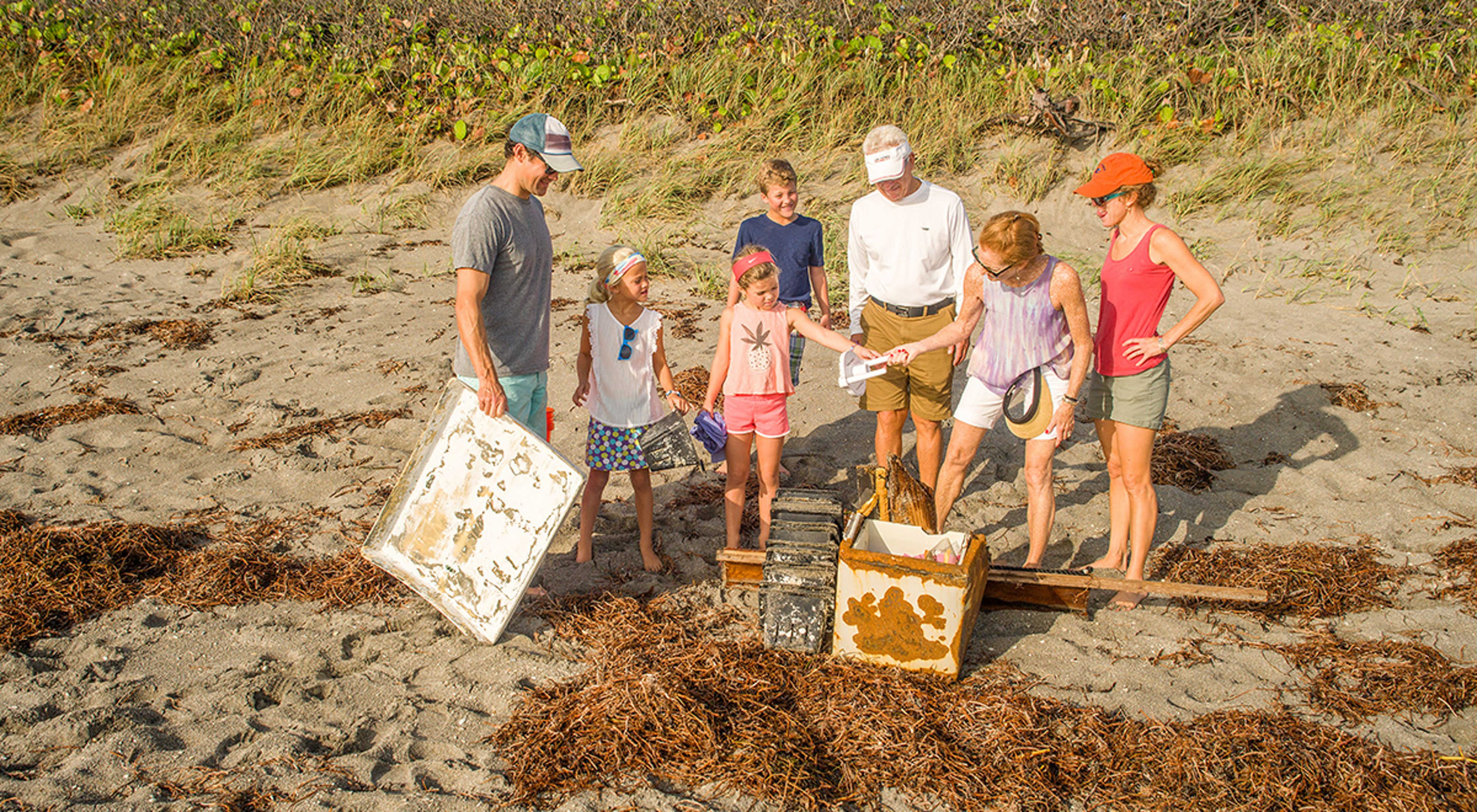 Family participates in a shoreline cleanup at Blowing Rocks Preserve