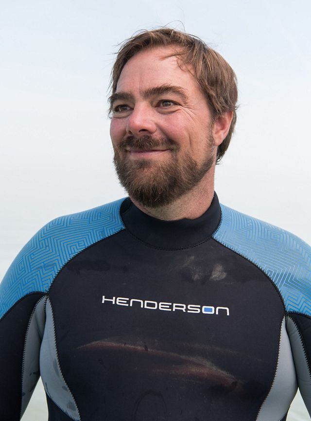 Portrait of a smiling man wearing a blue and black wetsuit.