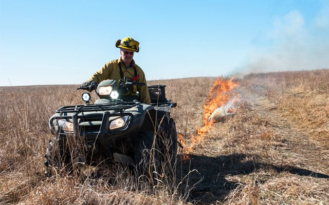 A burn boss lights a controlled burn on the preserve.