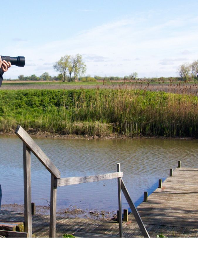 A man taking photos with a camera at Erie Marsh
