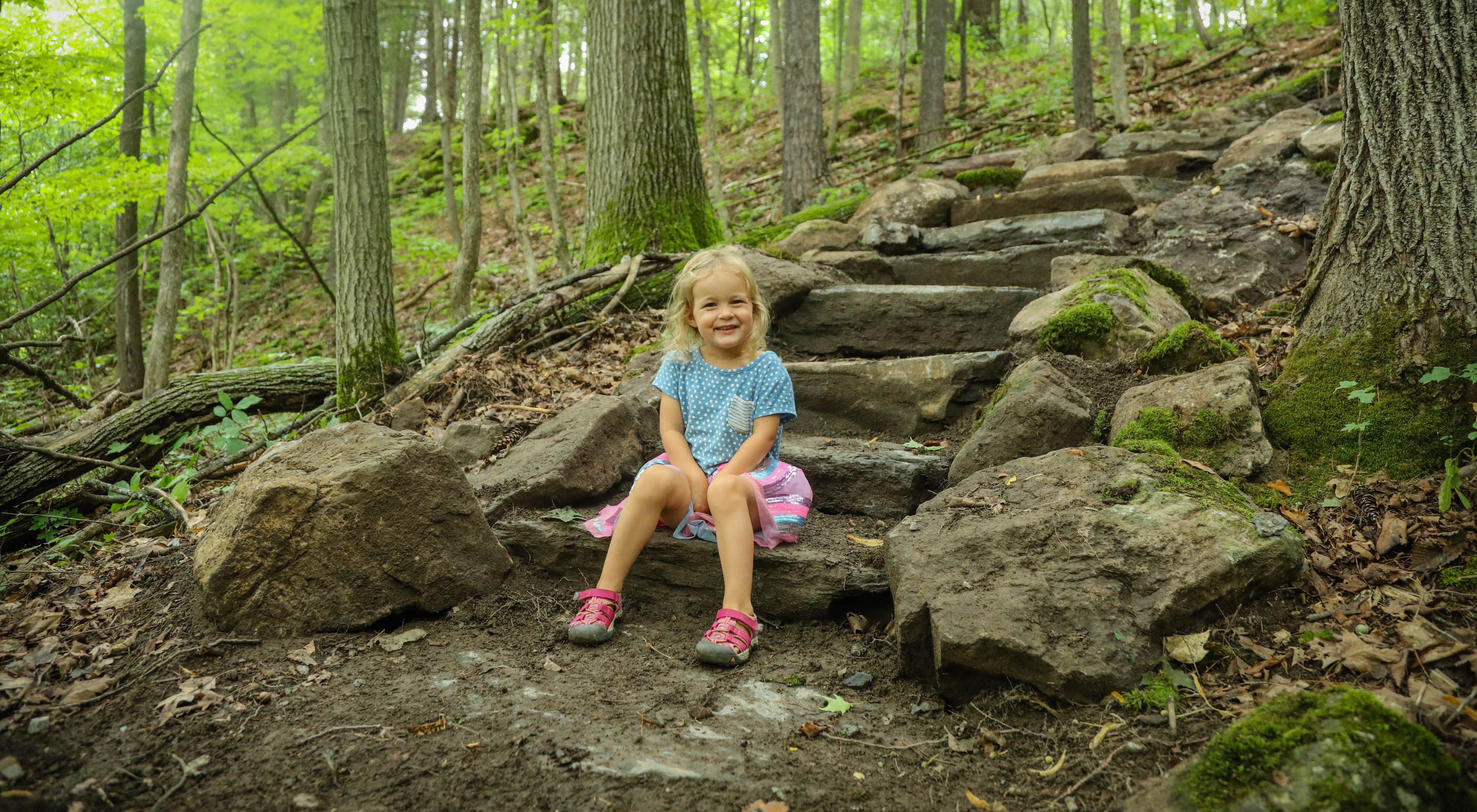 A girl sits at the trailhead at our Boquet River Nature Preserve
