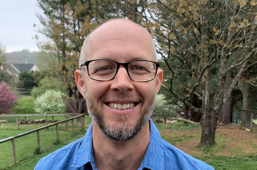 Close head shot of Clinch Valley Program Director Brad Kreps. A smiling man wearing glasses and a blue shirt poses outdoors.