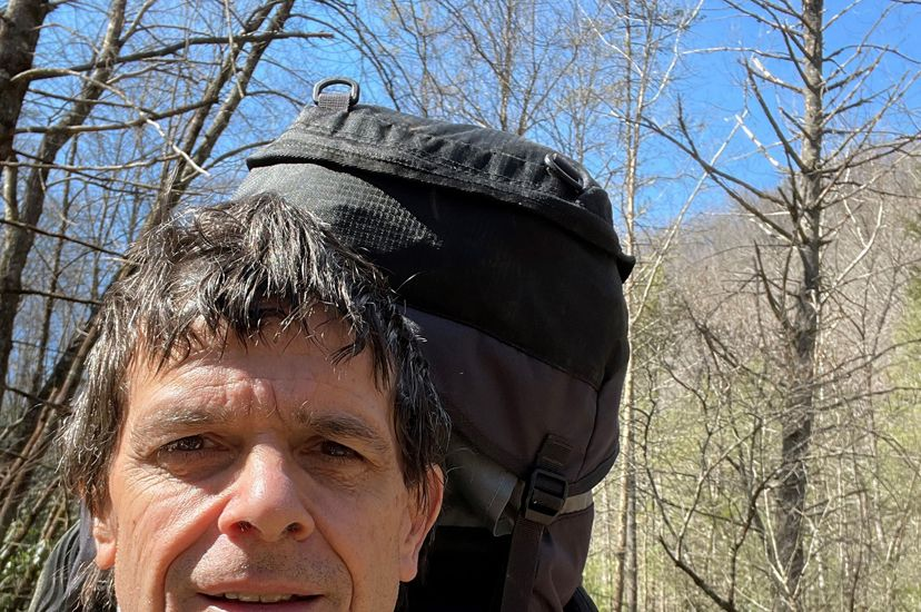 Candid photo of Clinch Valley Ecologist Braven Beaty. A man takes a selfie during a hike. He is wearing a green jacket and a large pack that extends above his head. A wide trail bends away behind him.