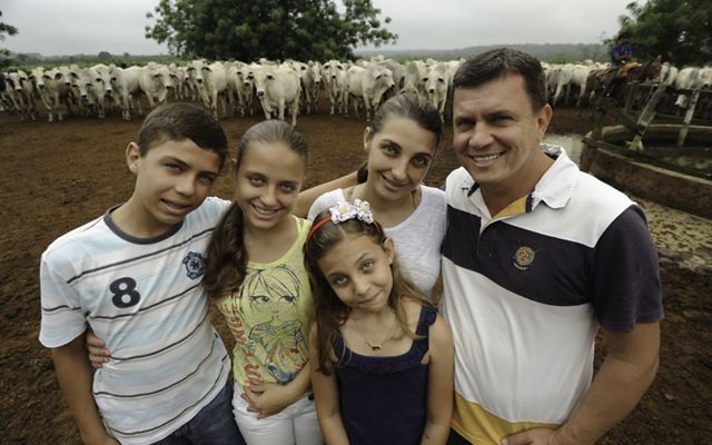 Family photo in front of cows.