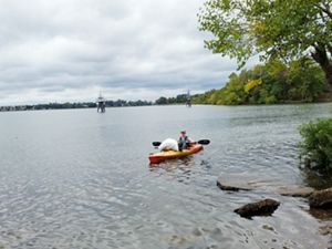 A person floats in an orange kayak in shallow water just offshore of a marsh area. A large white trash bag sits on the kayak's prow, part of a volunteer clean up effort.