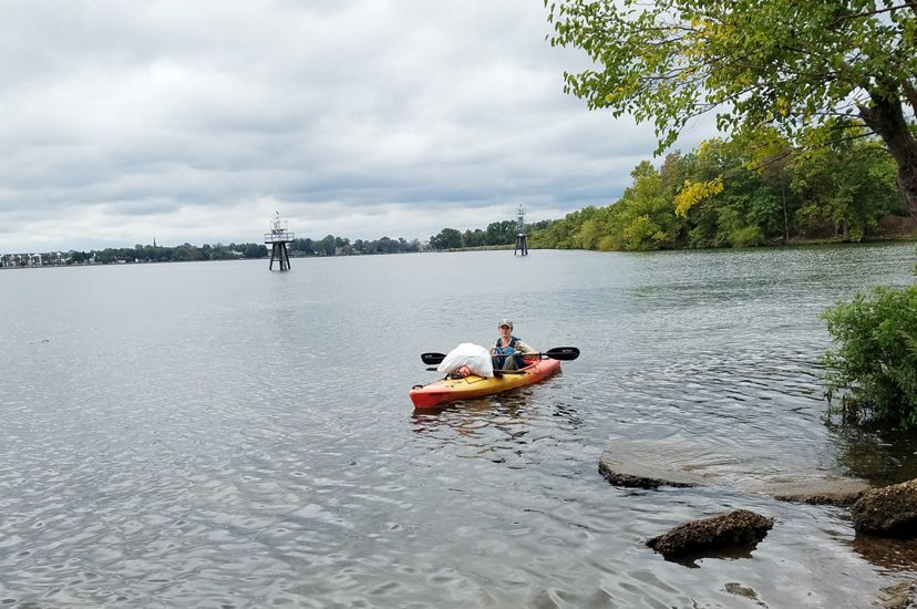 A woman wearing a PA DCNR uniform and cap floats in a kayak in a wide marsh. There is a large white bag of trash balanced on the bow of the orange kayak, collected during a volunteer event.