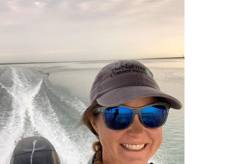 Candid snapshot of Marine Restoration Specialist Brittany Gonzalez. A smiling woman wearing sunglasses and a ball cap drives a small boat in open water.