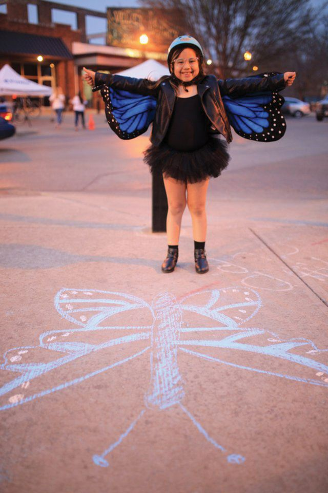 A young girl shows off her wings at a street festival celebrating Earth Day.