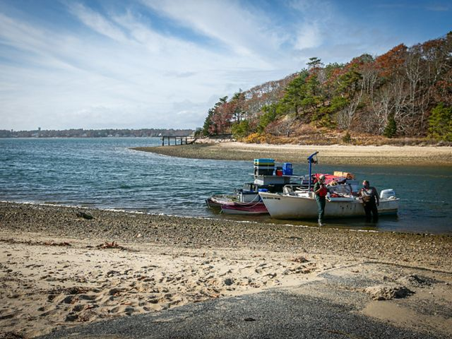 View from the sand of the entrance of a bay, with two boats anchored on shore in the foreground, and land with autumnal trees in the background.