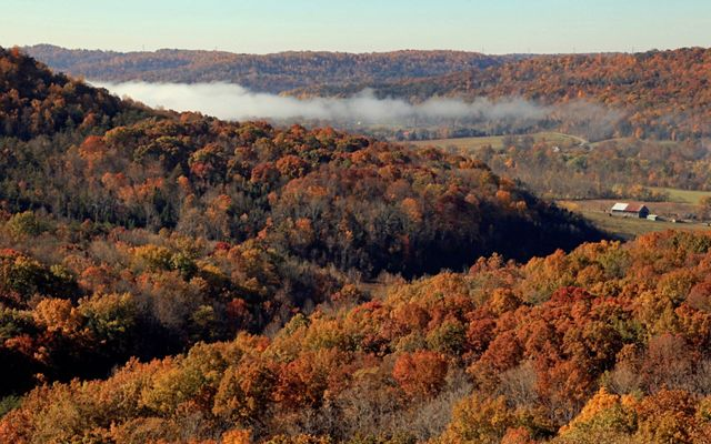 Overlooking forested hills of yellow, brown, orange, and muted red foliage that lead into a valley field with a barn.